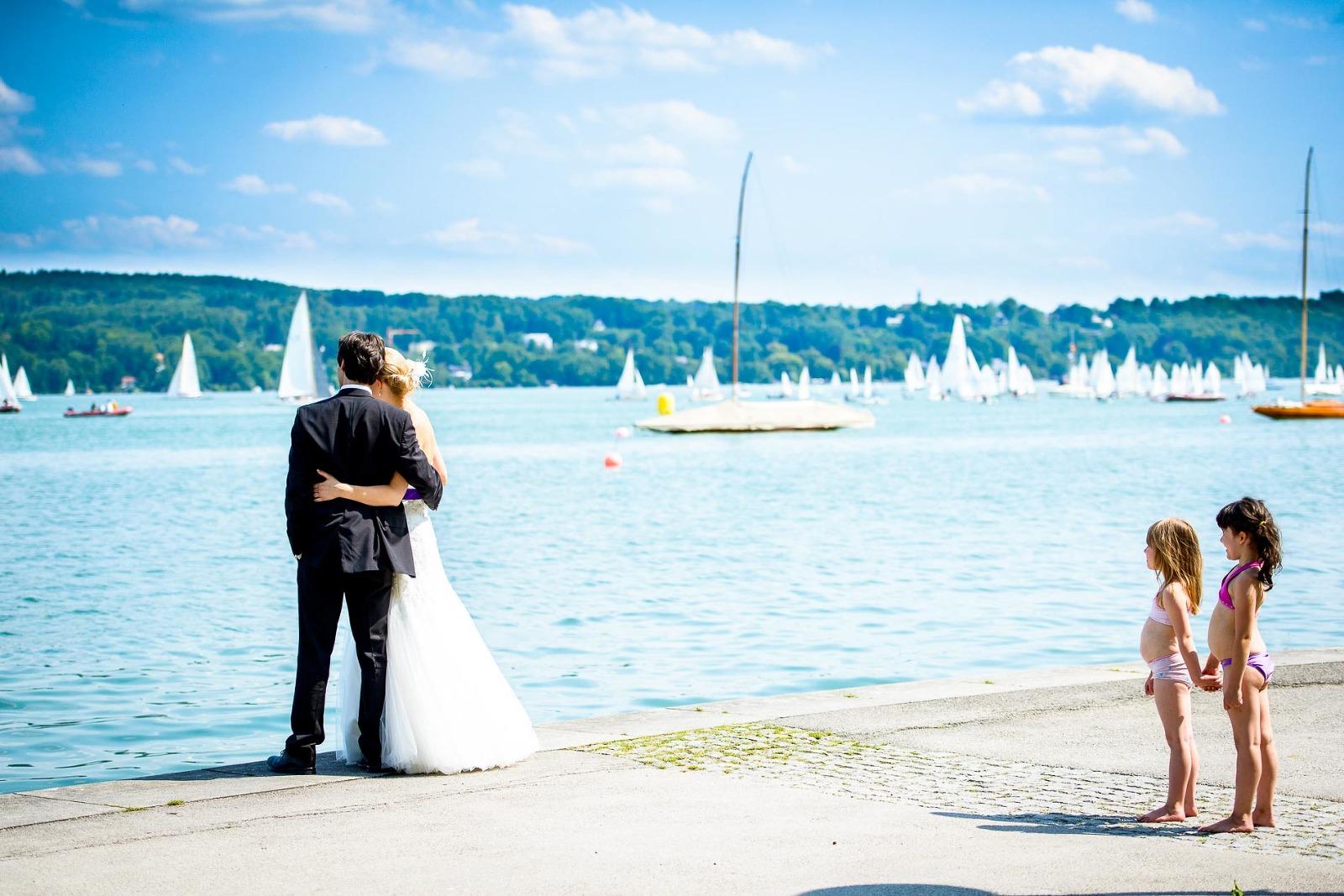 Hochzeits-Fotografie Starnberg, Brautpaar am See und kleine Kinder in Badekleidung an der Uferpromenade