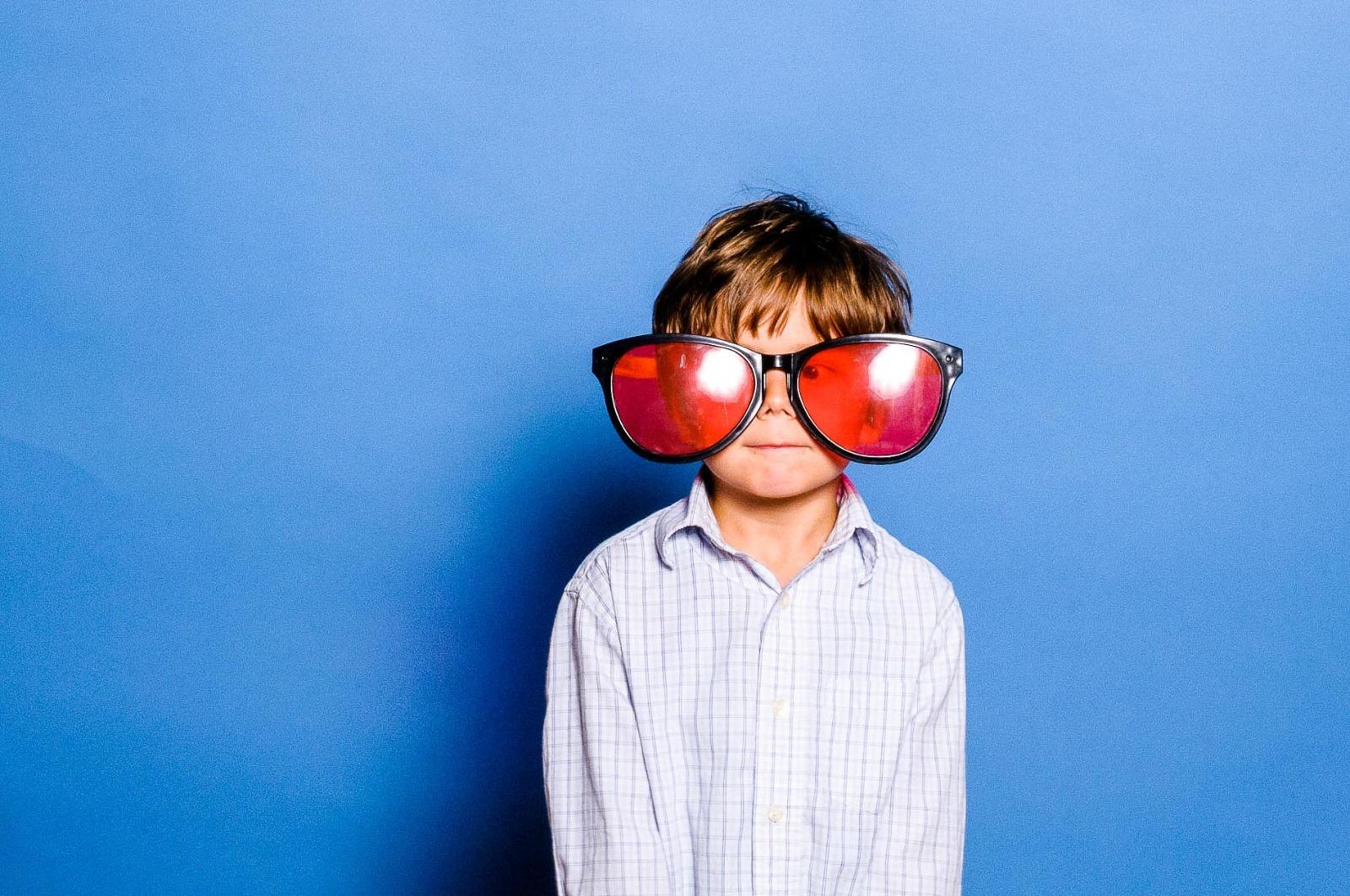 Hochzeits-Fotografie München, Kind mit Riesenbrille vor der Fotobox